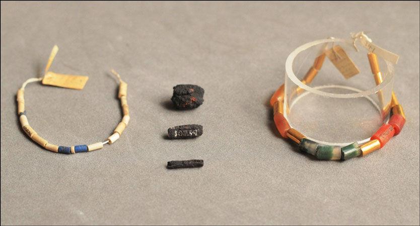 METEORITT-SMYKKER: Meteorittjern-bitene ligger i midten av bildet. Bildet viser også sylinderne med blå lasurstein (til venstre), og rødlig karneol, agate og gull (til høyre), som meteorittjern-sylinderne opprinnelig var tredd sammen med. Foto: UCL Petrie Museum/Rob Eagle
