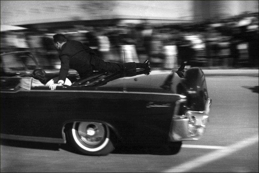 SEKUNDER ETTER: Dette bildet er tatt like etter at det ble avfyrt tre skudd mot presidentens kortesje i sentrum av Dallas. Sikkerhetsagent Clint Hill har kommet løpende i bilen bak, mens Jackie Kennedy ligger sammenkrøpet i baksetet. Foto: AP