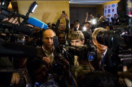 VILLE TILSTANDER: Her forsøker Magnus Carlsen og pappa Henrik Carlsen å trenge seg gjennom det internasjonale pressekorpset. Foto: Erlend Aas / NTB scanpix