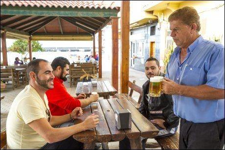 ALDEA: Strandrestaurantene her blir mest brukt av kanariske turister. her serverer Paco Ramirez Seguna øl til vennene Enrique Reyes Pérez (31), Ruben Tena Palacios (30) og Cristian Silva Casimiro (26) som er på søndagstur fra Telde.