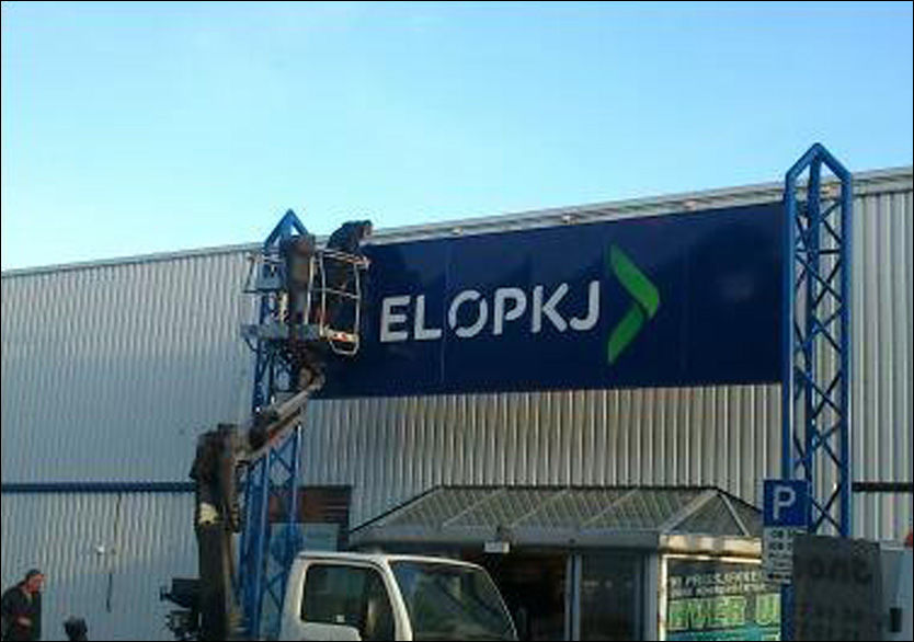 VILT SKILT: En skiltmontør er i gang med å montere det nye, store skiltet over hovedinngangen på Elkjøpbutikken i Bodø. Foto: Siw Falch