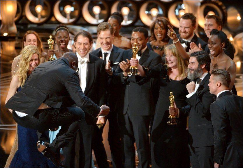 HOPPENDE GLAD: Steve McQueen hopper av glede foran skuespillerne og deler av teamet fra «12 Years a Slave», som vant Oscar for beste film. Foto: AP