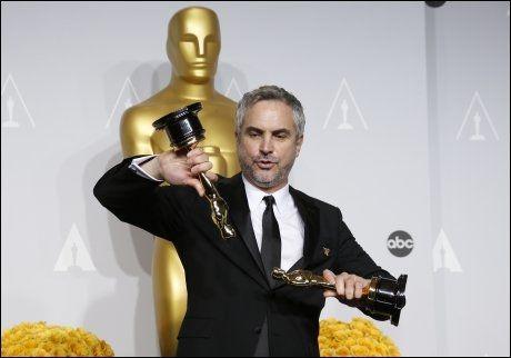 LEKTE MED OSCAR: Regissør Alfonso Cuarón med to av Oscar-statuettene «Gravity» fikk natt til mandag. Foto: Reuters