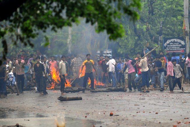 GATESLAG: I juli 2010 satte rasende tekstilarbeidere opp barrikader og kastet stein på sikkerhetsstyrker i forbindelse med protester mot de lave lønningene. Politiet svarte med tåregass og gummikuler. Foto: AFP