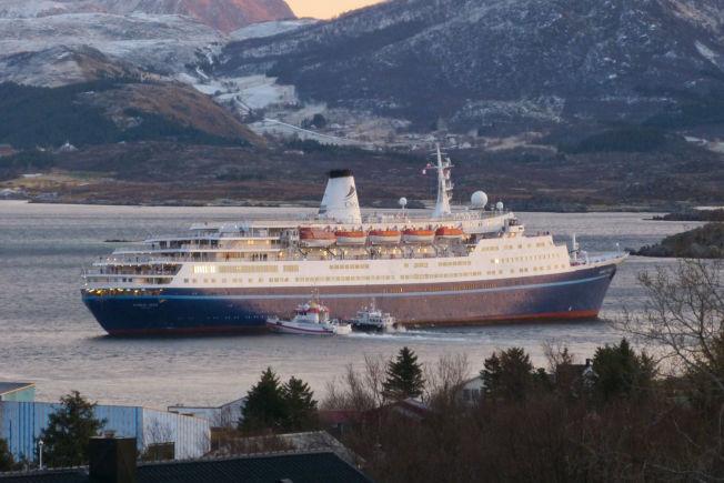 PÅ GRUNN: En redningsskøyte og taxibåt ankommer langsiden på cruisebåten lørdag morgen. En slepebåt arbeider nå med å få skipet fritt.