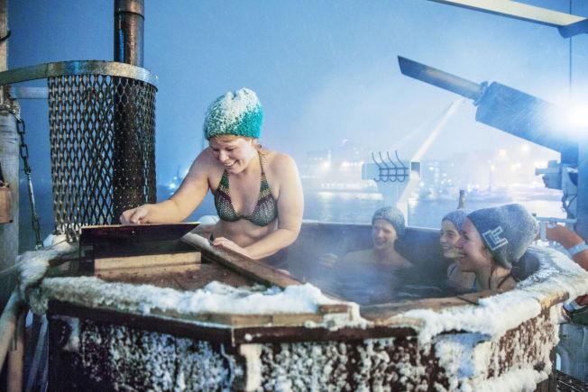 <p>FYRER MED VED: Marte Aasen legger i en vedkubbe i saltvannsstampen på dekk, til glede for Joar Nivfors, Silje Haaland og Katrine Blom, som alle valgte å ha lue på under badeseansen i kulden.<br/></p>