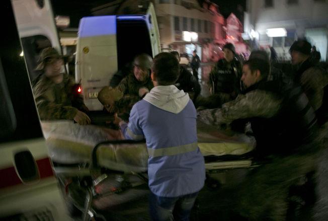 <p>FLERE SÅREDE: Spesialstyrken i Makedonia bærer ut sårede kolleger ved åstedet der åtte politifolk mistet livet lørdag kveld. 30 politifolk ble såret i opptøyene.<br/></p>