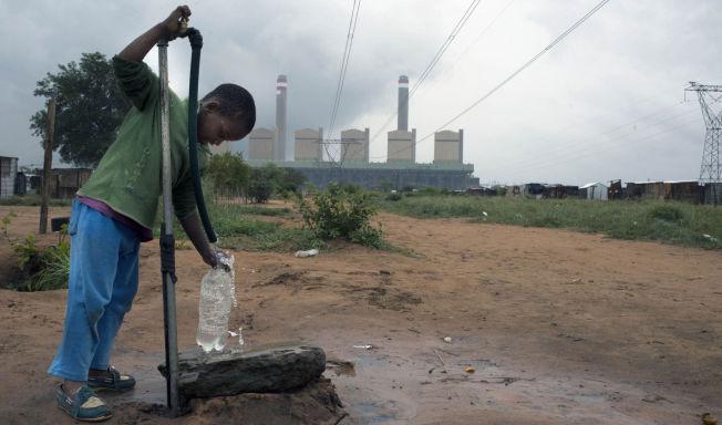 <p>KULL PÅVIRKER: Miljøskadene merkes godt lokalt av befolkningen i Sør-Afrika. Her henter en ung gutt vann foran kullkraftverket i Matimba. Vann er en manglevare i hele Waterberg-området, og kullgruver og kullkraftverk forverrer dette.</p>
