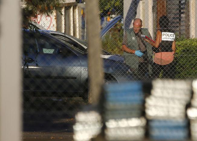 Fransk politi undersøker en bil og ser etter bevis hos et transport- og leveringsfirma under etterforskningen i Chassieu. nær Lyon i Frankrike.