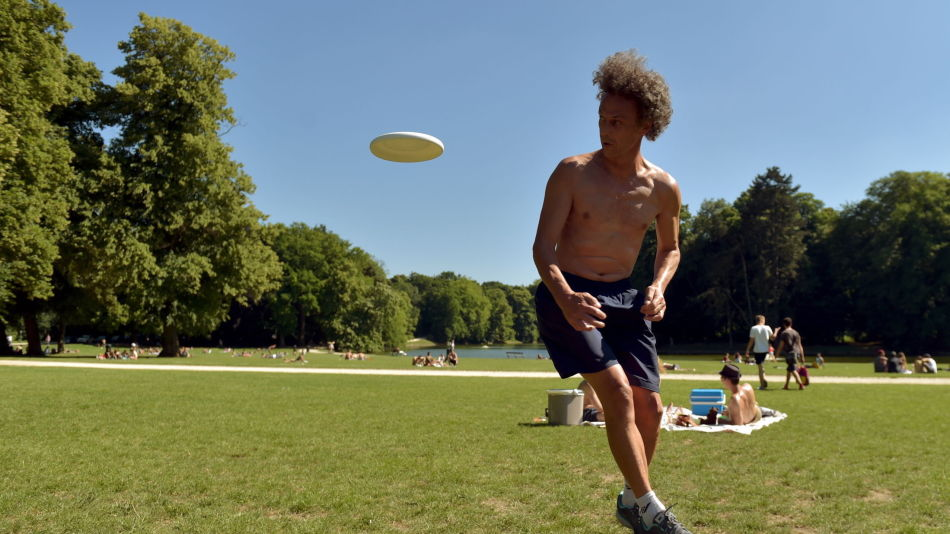 Man plays frisbee in a park during a heat wave in Brussels, Belgium