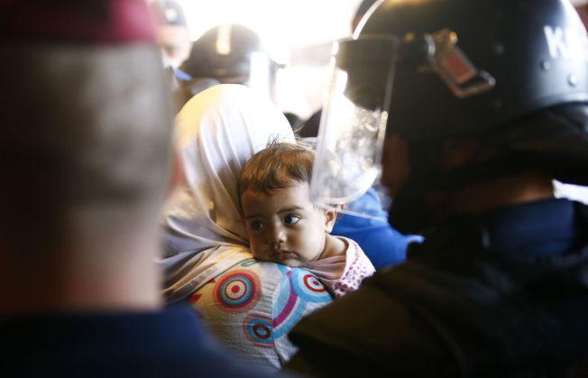 <p>POLITIBESKYTTELSE: En liten jente ser på politimennene som holder vakt ved flyktningene på jernbanestasjonen Bicske i Ungarn.<br/></p>