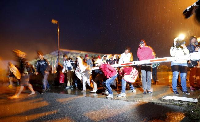 <p>VELKOMMEN TIL ØSTERRIKE: Her passerer flyktningene grensestasjonen Hegyeshalom på sin vei inn i Østerrike og videre til Tyskland tidlig lørdag morgen.<br/></p>