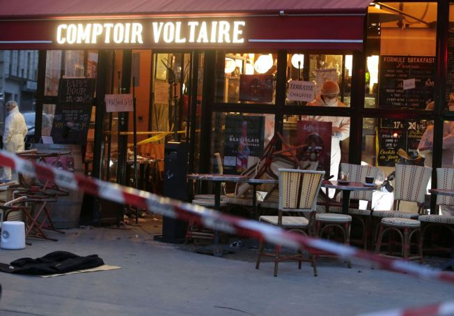 Forensic police search for evidences inside the Comptoire Voltaire cafe at the site of an attack on November 14, 2015 in Paris, after a series of gun attacks occurred across the city. AFP PHOTO / KENZO TRIBOUILLARD