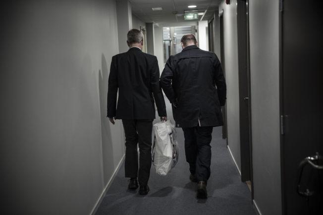 <p>IKKE I POSE OG SEKK: Robert Eriksson tusler ut av kontoret. I plastposen som hans kollega bærer for ham, er alt som Eriksson tok med seg fra departementet.</p>