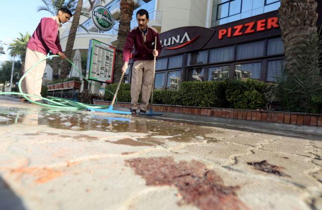 BLODPØL: Rengjøringsarbeidere vasker bort blod fra fortautet utenfor hotellet, lørdag morgen.