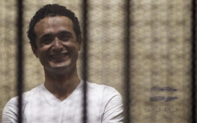 <p>LIVSTID: Den egyptiske aktvisten Ahmed Douma smiler i buret han ble plassert i under en rettssak i 2013. Han er fortsatt i fengsel.</p>