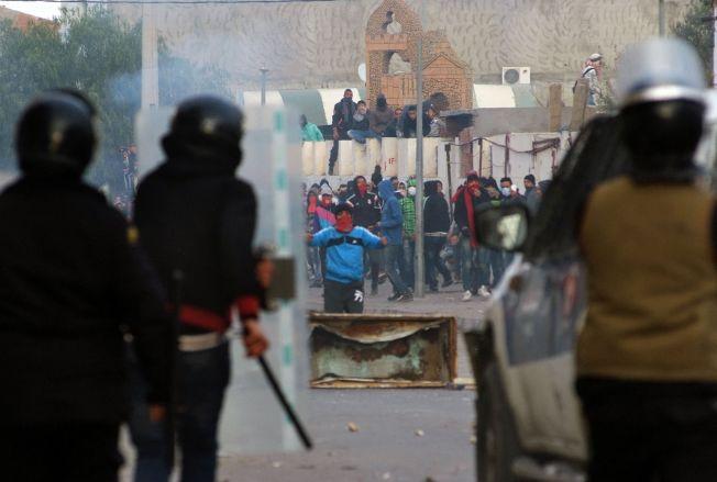 <p>GATEKAMPER: Demonstranter barker sammen med politifolk i Kasserine torsdag 21. januar.<br/></p>