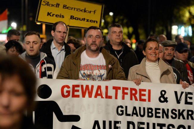 <p>TO TUNGER: Lederne av Pegida-bevegelsen i Tyskland, Lutz Bachmann og Tatjana Festerling, bærer et banner hvor det heter «Uten vold og forent mot troskrig på tysk grunn». Samtidig har Festerling kommet med det som kan oppfattes som oppfordringer til vold. Bachmann har på seg en t-skjorte med påtrykket «løgnpresse».</p>