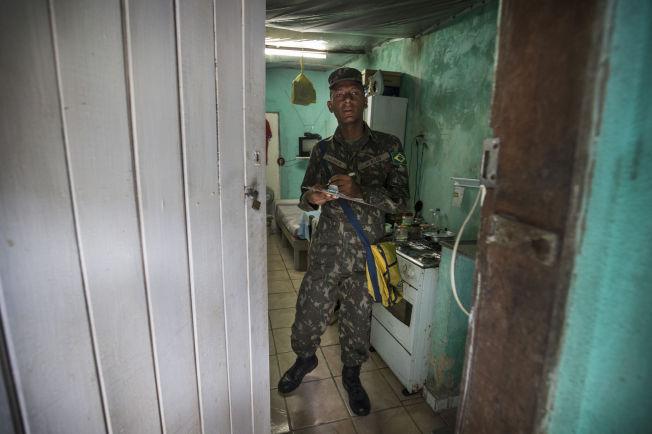 <p>PÅ JAKT: Mauricio (20) fra den brasilianske hæren inspiserer huset til Genivaldo (56) i slummen i Monteiro, Recife.</p>
