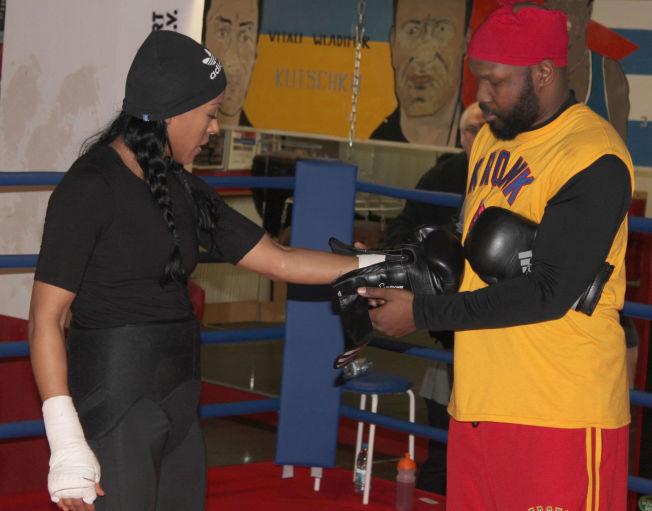 BESTEMT: Trener Johnathon Banks synes kvinnelige kampsportutøvere fortjener mer sportslig respekt, og at det er trist når de kaster klærne for å få oppmerksomhet. Her hjelper han Cecilia Brækhus på med hanskene på trening i Berlin.