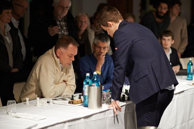 BRAGD: Jens-Erik Rudolph (innfelt) spiller til daglig i tysk 6.divisjon i sjakk. Men lørdag opplevde han sitt livs sjakkbragd da var den eneste av 70 deltagere som slo Magnus Carlsen i simultansjakk. På det store bildet tenker Carlsen ved brettet til Rudolph.