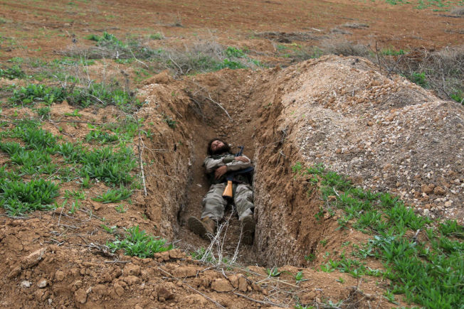 <p>PAUSE: En opprørssoldat sover med våpenet sitt i en grop i Al-Lataminah nord i Syria.</p>